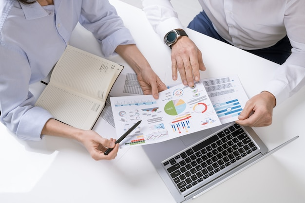 Mani di due mediatori contemporanei che discutono di documenti finanziari con grafici, tabelle e diagrammi alla riunione