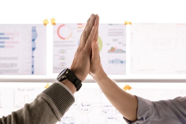 Mani di due soci d'affari di successo nel gesto di batti il cinque dopo aver fatto un accordo o un affare sorprendente