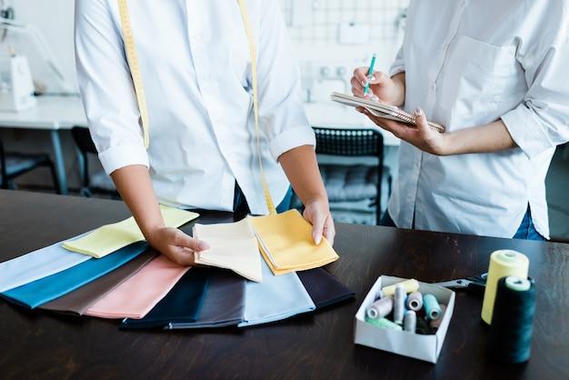 Mani di due giovani femmine che scelgono campioni tessili per la nuova collezione di moda e prendono appunti dal tavolo in officina