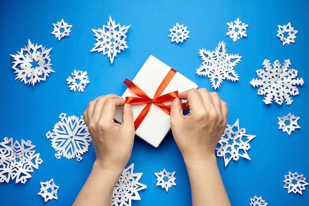 Mani che legano nastro rosso su confezione regalo bianca su blu con fiocchi di neve di carta