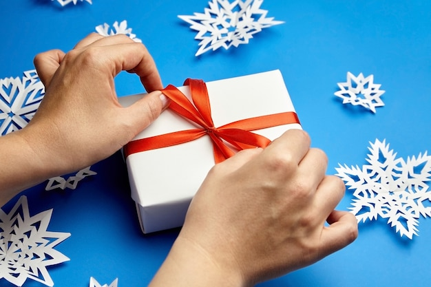 Mani che legano il nastro rosso sul contenitore di regalo bianco sull'azzurro