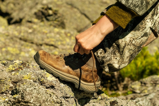 Mani che legano i lacci delle scarpe su un primo piano di uno scarpone da trekking consumato