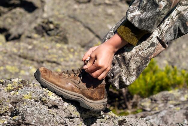 Mani che legano i lacci delle scarpe su un primo piano indossato di uno scarpone da trekking