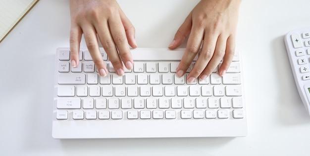 Mani che digitano sulla tastiera. mani di donna sulla tastiera lavorare a casa.