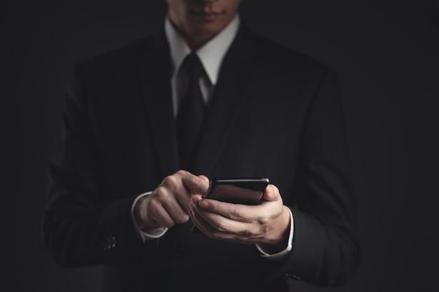 Mani digitando un messaggio su smart phone. bello imprenditore in abito nero.