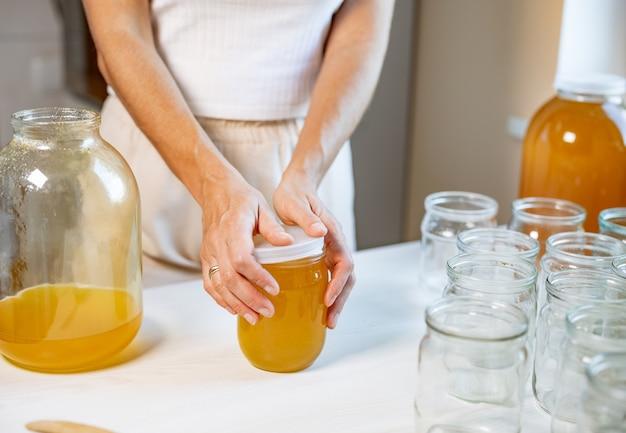 Le mani di una donna sconosciuta chiudono vasetti di vetro trasparente con puro miele dorato dolce con un coperchio di gomma, in piedi su un grande tavolo di legno bianco e accanto a un piccolo piattino con un cucchiaio di legno