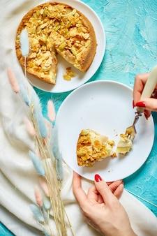 Le mani di una donna irriconoscibile mangiano un pezzo di torta di mele o pere con noci caramellate sul tavolo blu con luce solare