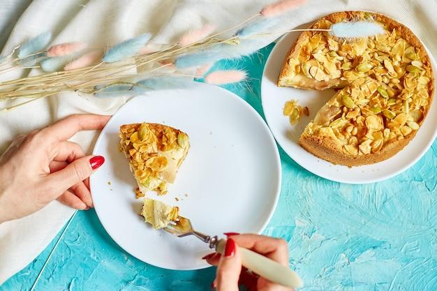 Le mani di una donna irriconoscibile mangiano un pezzo di torta di mele o di pere con noci caramellate