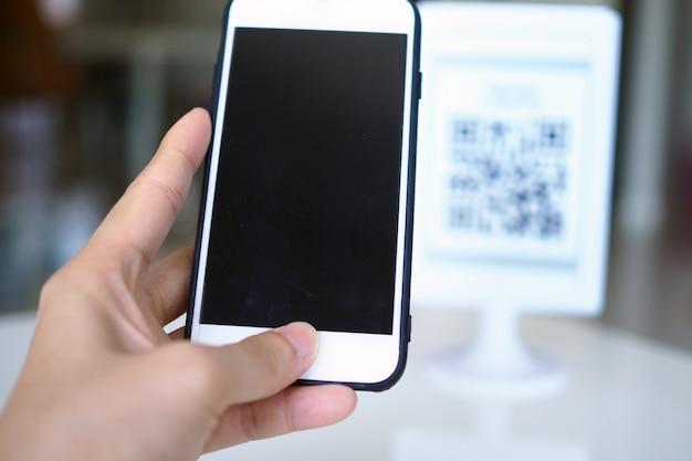 Le mani usano il telefono per scansionare i codici qr per ricevere sconti sugli acquisti.