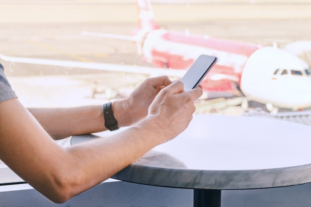 Mani che utilizzano un telefono cellulare all'aeroporto