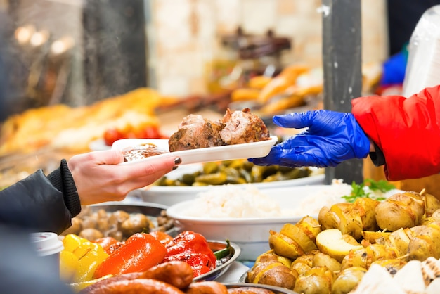 Mani del venditore che serve cibo sul mercato del cibo di strada
