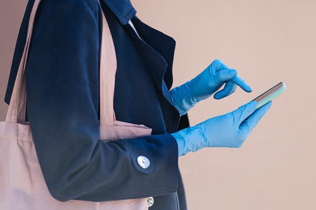 Mani che indossano guanti medici monouso, utilizzando lo smartphone durante l'epidemia di covid 19. protezione nella prevenzione del coronavirus. un concetto di consegna, servizio online, app.