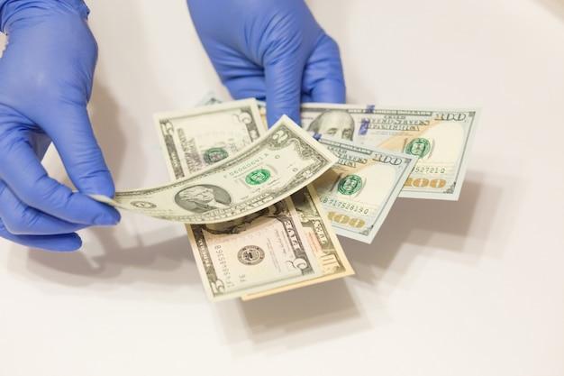 Mani che indossano i guanti medici che contano le banconote del dollaro su superficie bianca. messa a fuoco selettiva