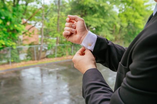 Mani dello sposo del matrimonio che si preparano in abito mano dello sposo sposa che si prepara per il matrimonio
