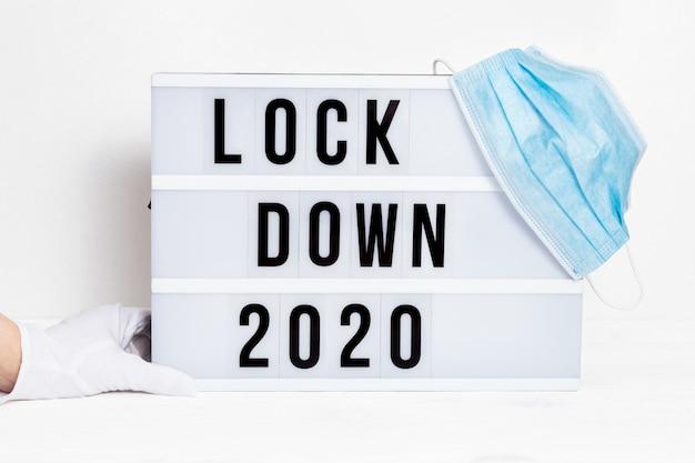 Le mani nei guanti bianchi tengono la scatola luminosa con blocco dei messaggi 2020 e maschera protettiva chirurgica.