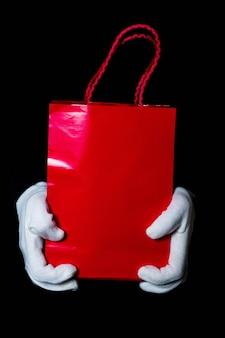 Le mani in guanti bianchi tengono un sacchetto di carta su uno sfondo nero
