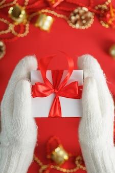 Mani in guanti lavorati a maglia bianchi che tengono un regalo su uno sfondo rosso. scatola bianca con nastro rosso. stile di vita sostenibile per le vacanze. decorazioni natalizie