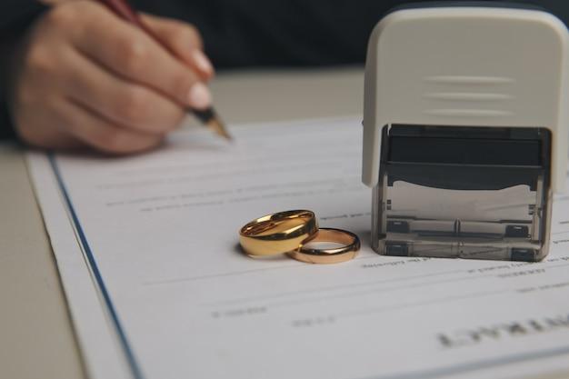 Mani della moglie, marito firma decreto di divorzio, scioglimento, annullamento del matrimonio, documenti di separazione legale