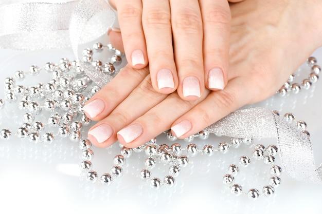 Mani con un bellissimo design invernale, nastro e perline isolate su bianco