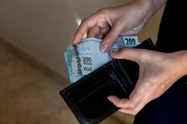 Mani con portafoglio nero che mettono soldi brasiliani.