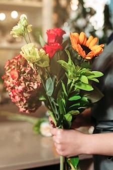 Mani con il primo piano del mazzo al negozio di fiori.