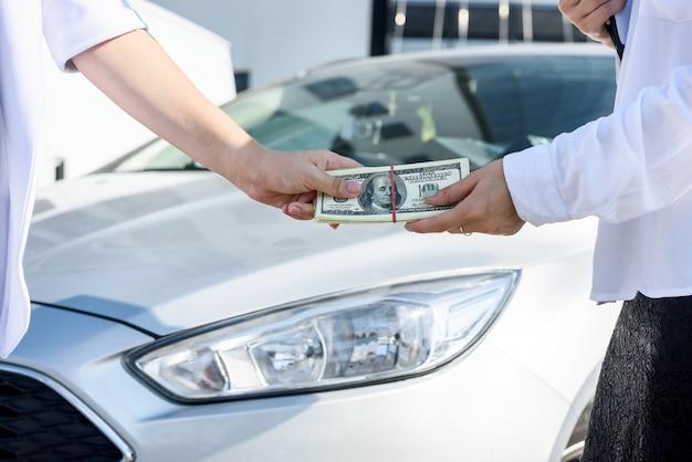 Mani con il pacco del dollaro sopra il cofano della macchina. vendita di auto o concetto di noleggio auto