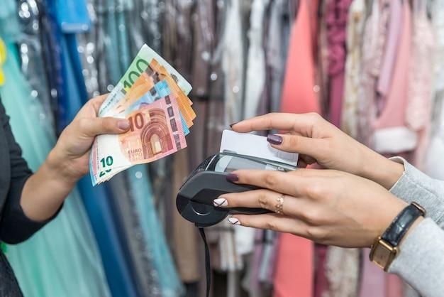 Mani con euro e carta di credito che pagano per l'acquisto