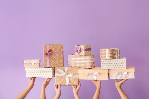 Mani con scatole regalo sul colore