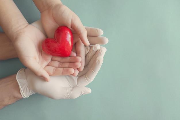 Mani con i guanti che tengono le mani del bambino e il cuore rosso, l'assicurazione sanitaria e il concetto di donazione