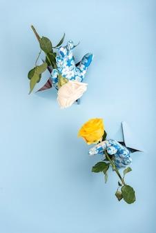Mani con guanti che saldano da un foro di fondo blu con due rose, gialle e rosa
