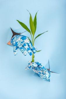 Mani con guanti che saldano da un foro inferiore blu con avocado di bambù