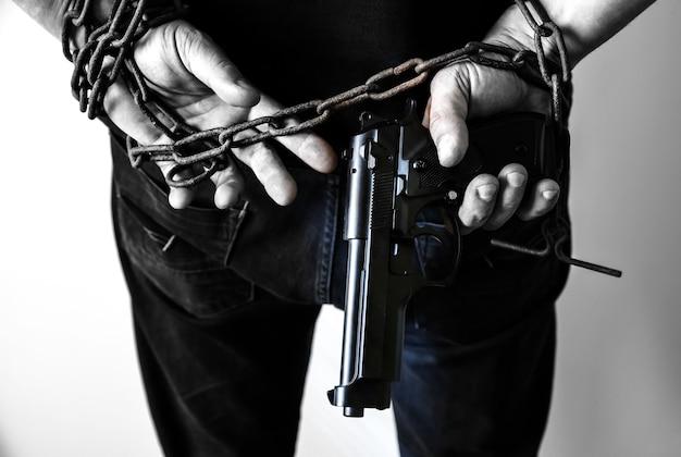 Mani con pistola in vecchie catene arrugginite. rapinatore arrestato per reato illegale. il rapinatore ha infranto la legge.