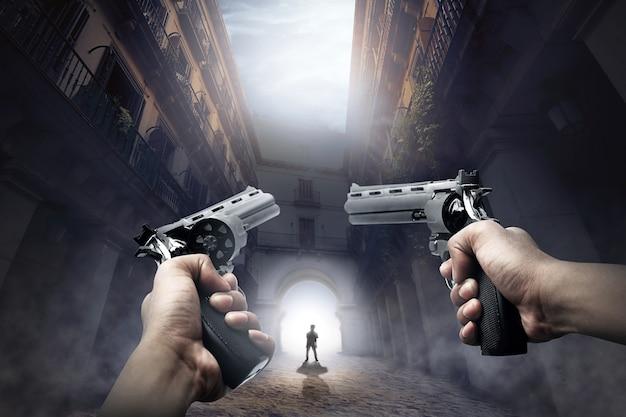 Mani con le pistole pronte a sparare allo zombi ambulante