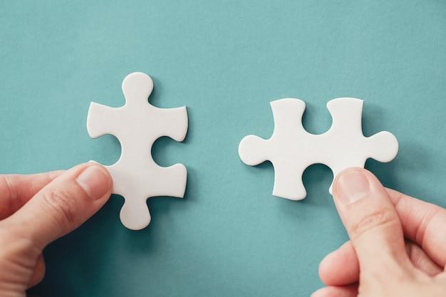 Mani con pezzi di puzzle, pianificazione della strategia aziendale, morbo di alzheimer, autismo e concetto di salute mentale