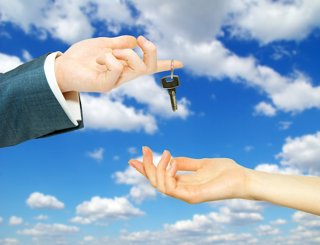 Mani con chiave su un cielo di sfondo