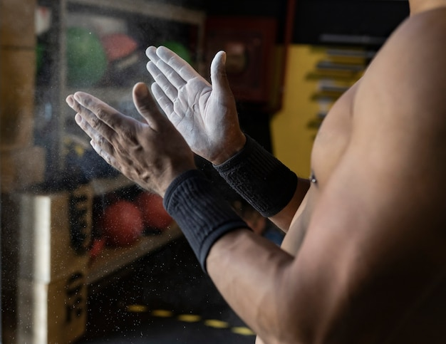 Mani con uomo di magnesio in una palestra