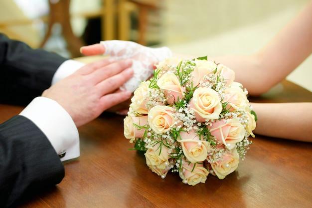 Mani con anelli e bouquet da sposa
