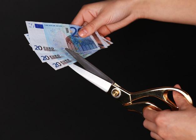Mani con le forbici che tagliano le banconote in euro, su uno spazio nero