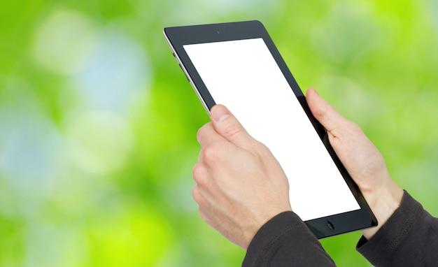Mani con computer tablet sul verde