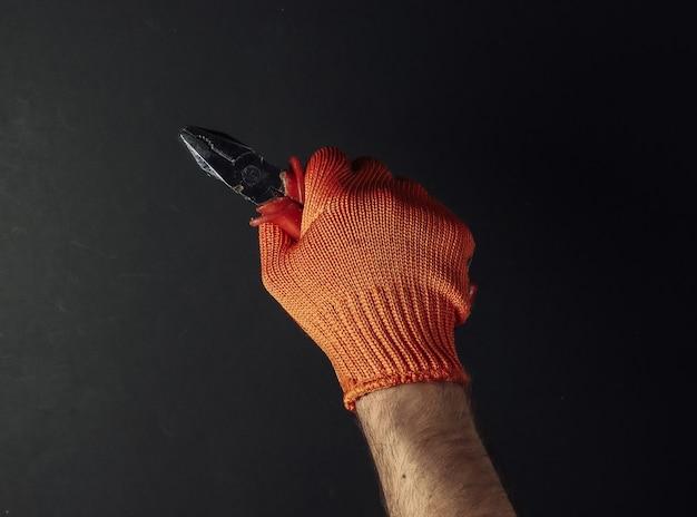 Le mani con i guanti da lavoro tengono le pinze su priorità bassa nera. operaio industriale