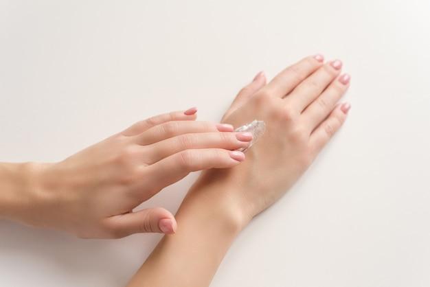 Mani di una donna che applica crema bianca