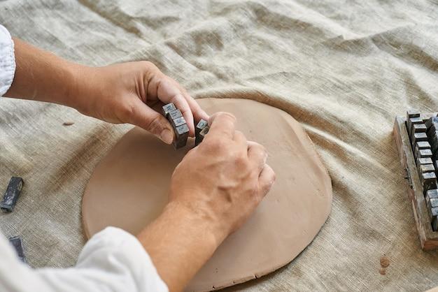 Mani di una ceramista artigiana che impasta uno strato di argilla sul primo piano del tavolo