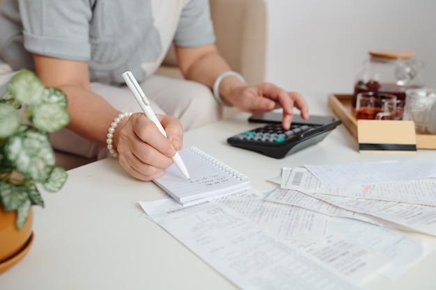 Mani di donna che controllano le bollette non pagate, fanno calcoli e prendono appunti nel pianificatore