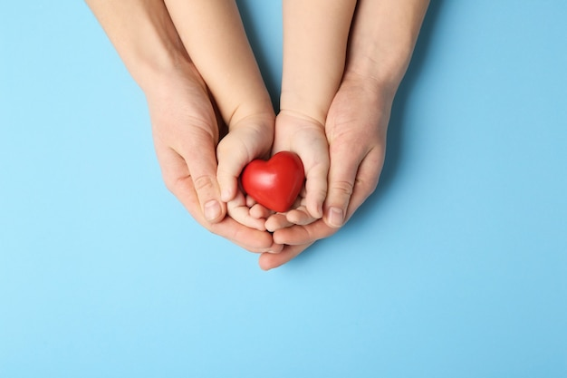 Mani di donna e bambino con cuore rosso sulla superficie del colore. concetto di cardiologia