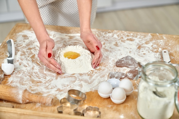 Mani della donna che cucinano pasta sul bordo di pasticceria.