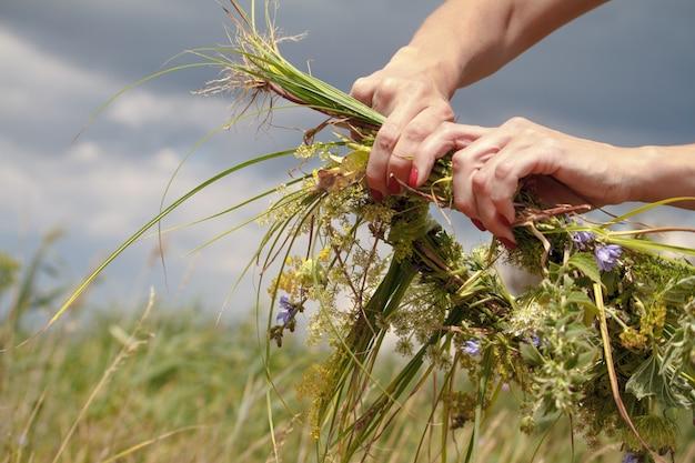 Mani della donna che elaborano la corona dei wildflowers su un cielo nuvoloso blu