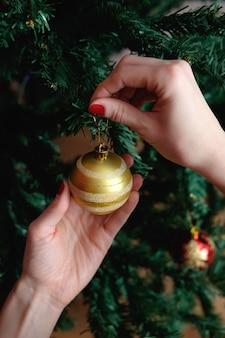 Mani della donna che decora l'albero di natale