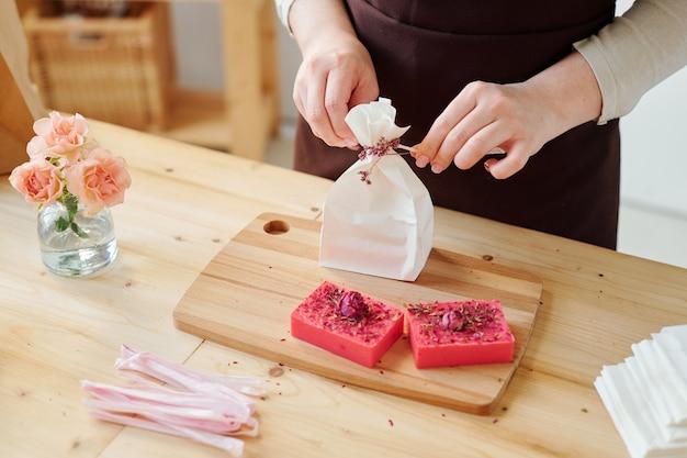 Mani di donna che decora il pacchetto di carta con fiori secchi mentre confeziona saponette fatte a mano dal posto di lavoro