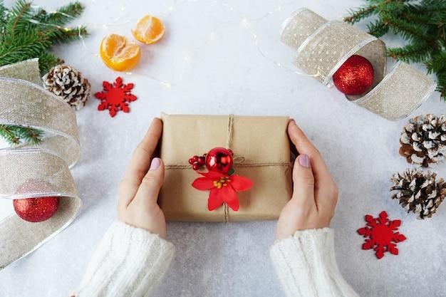Mani della donna che tiene il contenitore di regalo di natale con decorazioni invernali