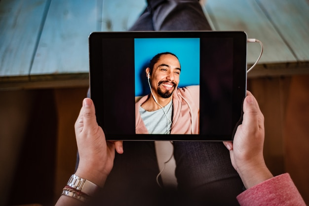 Mani di una donna che tiene una tavoletta digitale mentre parla con un uomo in una videochiamata